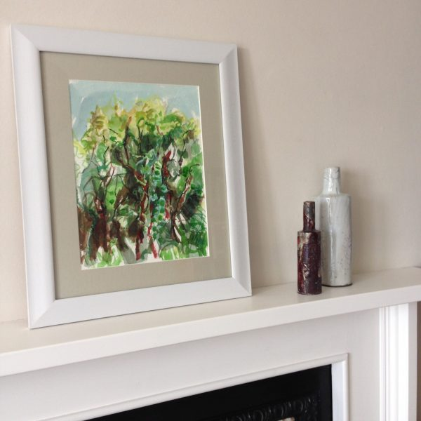 a photograph of a framed gouache painting on a mantelpiece title 'Orchard Woodland' by artist Catherine Coulson © 2019 Catherine Coulson